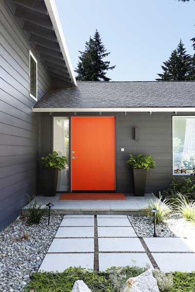 The exterior of the front door has been painted bright orange, a reference to the shipping containers' (painted over) Cor-Ten steel. From the street, this is the only indication of what lies inside.