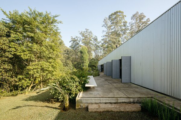 The living and dining areas open to a concrete deck overlooking the garden through minimalistic openings in the corrugated-sheet cladding. The expansive decks and verandas at both the front and rear of the home essentially double the living space.