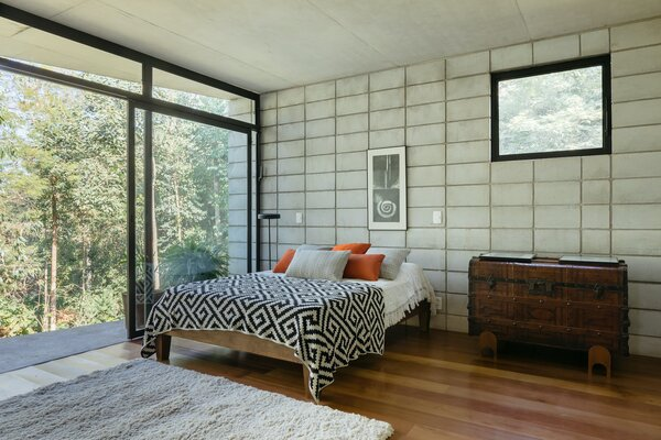 The main suite—including a bedroom, closet, and bathroom—is located in a concrete block structure at the far side of the home, separating it from the rest of the living spaces. The concrete blocks help to define it as a more private, personal space.