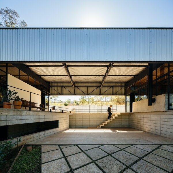 The carport-style garage is situated at the center of the home with the living spaces arranged around it in two volumes. Concrete stairs lead from the lower level to the main living level on the upper floor.