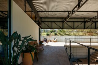 Generous walkways and verandas around the open garage expand the living space outside and connect the two living volumes.