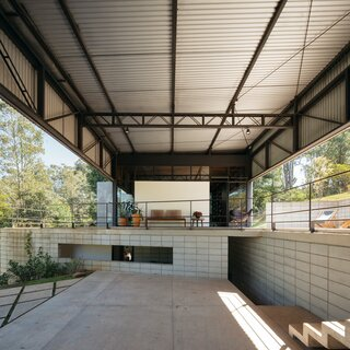"""The garage and the verandas play an important role in the relationship between external and interior spaces,"" says architect Gaú Manzi. ""From the garage, one can see the landscape through the house itself and into the living room, kitchen, and library, as the construction is rather transparent."""