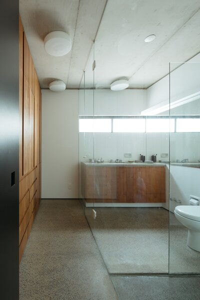 The main bathroom features warmly crafted timber joinery contrasted with terrazzo-style concrete floors and industrial concrete ceilings.