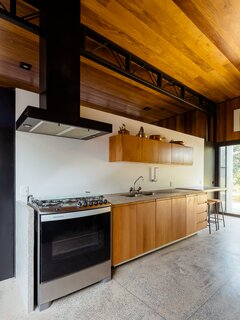 The kitchen is located behind the dining space and features a concrete counter—a reference to the industrial-style architecture.