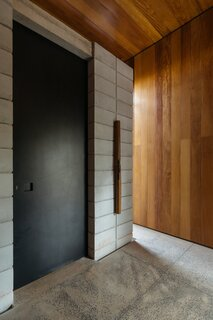 Industrial black metal doors—such as the entrance to the main suite—offset the internal timber cladding, reenforcing the contrast between the architecture and the interior.