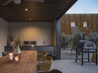 The ceiling of the exterior patio and soffits is crafted from inexpensive sheets of plywood cut into smaller pieces, assembled in a custom pattern, and stained.