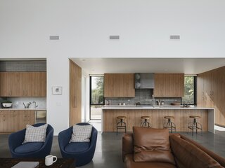 The kitchen and wet bar open out into the living area. Timber joinery adds warmth to the interior and contrasts with more industrial materials, such as the steel and concrete.