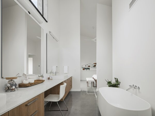 A large en suite bathroom adjoins the principal bedroom, featuring bright-white walls that reflect natural light and high windows that frame the sky.