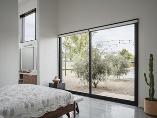 "The master bedroom features exposed aggregate concrete that blurs the transition as you step outside. ""The new desert landscape comes right up to it,"" says architect Cavin Costello."