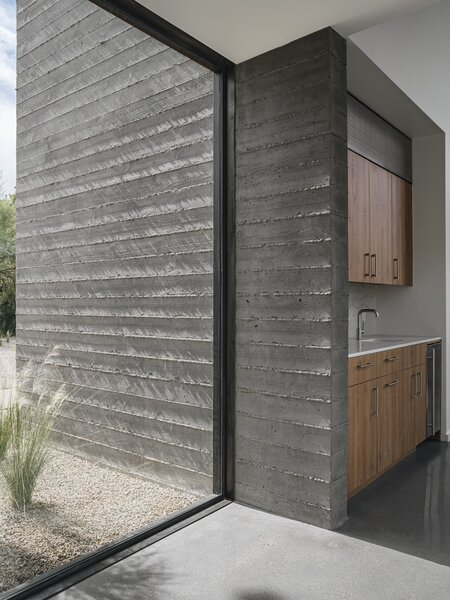 """Large glazed walls connect the different functional volumes of the home. """"You are constantly aware of the landscape as you walk from one area of the house to the next,"""" says Costello. This impression of the landscape being a part of the home itself is emphasized by the continuation of the board-formed concrete from exterior to interior."""