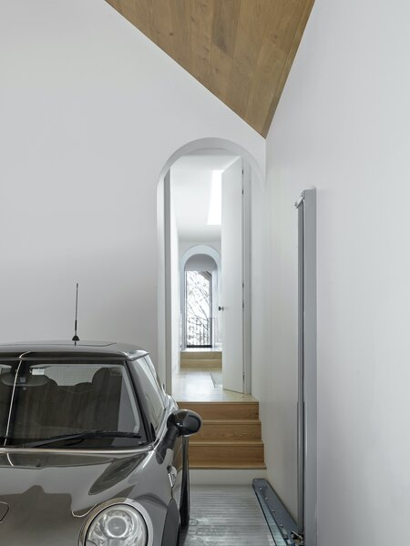 The pitched-roof garage features a four-car stacker, which makes clever use of an existing cellar under the old garage. The arched doorway leads from the garage into the hallway on the first floor.