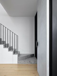 """The stair is crafted from Ceppo Di Gre stone that was supplied and installed by Granite Marble Works. """"There is just one quarry that mines it, and it has the most beautiful sedimentary quality with big dramatic flecks of white and black amongst its pebbly composition,"""" says architect Bronwyn Litera."""