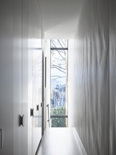 A three-story-high window at the rear of the home allows light and views to penetrate even the narrow hallway.