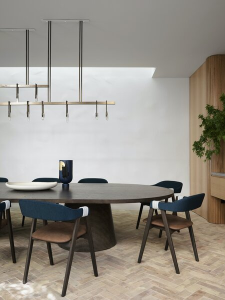 The floor in the dining room—which extends out to the entrance courtyard—is made of recycled terra-cotta roof tiles sourced by Gather & Co. and laid in a herringbone pattern. The dining room features a Butterworth table by Lowe Furniture and Mathilda chairs by Patricia Urquiola for Moroso.