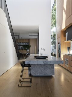 The kitchen sits at the center of the home beneath the void. Beneath the stair, sliding pocket doors conceal a pantry and kitchen appliances (such as the toaster and kettle).