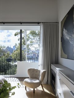 "The main bedroom has bifold steel-framed doors which tuck back to almost nothing, allowing the small balcony to become an extension of the main bedroom. ""Behind the framing of the balustrade and the canopy of the tree, the bedroom feels like a perfect retreat from the world,"" says architect Bronwyn Litera."
