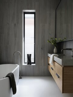 The use of raw, natural materials continues into the bathrooms, which feature timber joinery with concrete countertops that appear to float weightlessly.