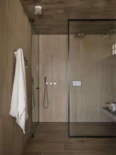 The shower features timber-look tiles supplied by Earp Bros, with a cast concrete bench that mirrors the materiality of the living spaces in the home.