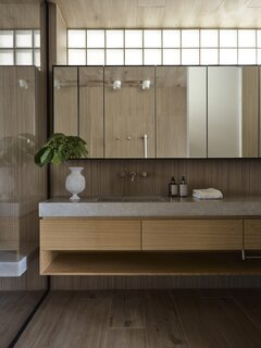 The cast concrete countertops in the bathrooms have a soft texture that complements the timber.