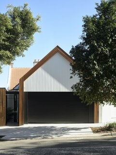 """The site in Darling Point is on a winding street leading up a hill, and the new architecture is designed to express the pitched-roof language of the original terrace house. """"It's incredibly steep at the back, which means the house looks rather modest from the street front—just a pitched-roof garage and a gate,"""" says architect Bronwyn Litera. """"At the rear facing Rushcutters Bay, however, it drops away over a height of five stories. The house is also in a heritage conservation zone, which meant that the existing roof line and chimneys needed to be retained. We worked closely with TC Build to form a 'plan of attack,' which involved propping the two long walls and the roof, and completely gutting the interiors."""""""