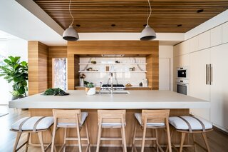 "The kitchen has a large central island, with the range and workspaces on the right and a huge built-in on the left in front of the stair. A bright, white laminate wall holds the oven and refrigerator. Architect Nicholas Fiore says this element ""pumps the brakes a bit"" on the white oak shiplap walls and white oak ceiling."