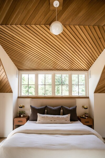 "The master bedroom opens to the northern balcony, which is set on a 10-foot-deep steel cantilever covering a patio below on the main level. ""The primo swag built-in feature is the white oak lap-sided ceiling in the master bedroom,"" says architect Nicholas Fiore. ""As architects, we set as a goal on every project to experiment in our details and to try something new. Turning lap siding on its head—literally—completely frees it from its conventional usage, and provides a rich texture on the ceiling surface. It also serves to pull together a tricky space created by the variegated ceiling planes, which were a result of the challenges served up by zoning and district guidelines."""