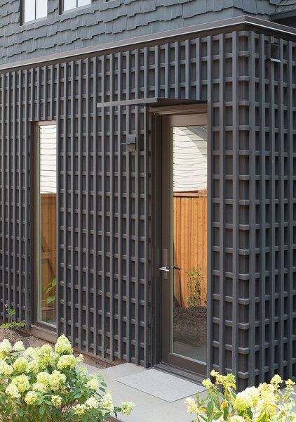 "The exterior walls of the mudroom are clad in a trellis—a historic feature commonly seen in the neighborhood, rendered here in a modern expression. ""The exterior is clad entirely in western red cedar, painted as required in the historic district,"" says architect Nicholas Fiore. ""Cedar has excellent rot and insect resistance, and takes paint beautifully—although we admit it was very hard to paint it once it was installed in all of its honey-tone glory!"""