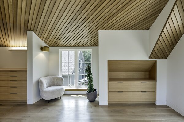 """The master suite features a sitting area and timber built-ins. """"Our team of trim carpenters practically lived in the house for a year,"""" says architect Nicholas Fiore. """"The value of built-ins is multifaceted, and it runs from the ephemeral to the most pragmatic."""""""