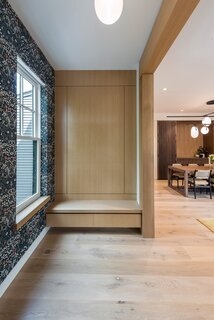 """The formal entry space features a built-in bench and is defined by a timber detail that runs up the walls and across the ceiling. """"Built-ins are an excellent way to bring a human scale to a project,"""" says architect Nicholas Fiore. """"People seek an intimacy—a coziness—in their homes, and we think that niches, window seats, benches, nooks, and other 'hand-scale' details can satisfy that human need."""""""