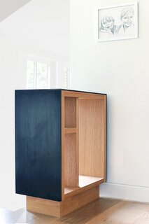 """A steel-and-wood built-in """"shoe drop"""" cabinet at the top of the stairs prevents things from piling up at the top step. As the design progressed, the home became more thoroughly """"built-in,"""" and nearly every room has custom features, including desks, windows seats, benches, cabinets, and panelling. """"This is an echo of the many craftspeople who set up shop in the nearby homes in the district 100 years ago, installing custom wood panels, handrails, built-ins, and bookshelves,"""" says architect Nicholas Fiore."""