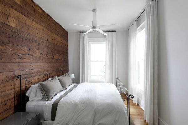 The original bedroom—now a guest room—features modern ceiling fans that offer a hint of the contemporary design to come in the addition, while the restored shiplap timber walls speak of the home's heritage.