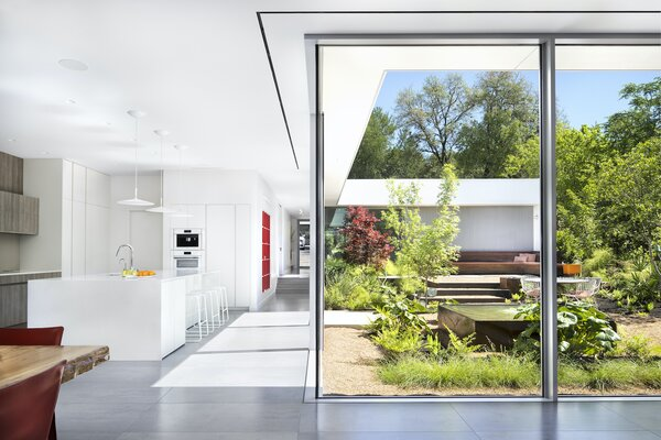 """The floor-to-ceiling sliding doors and windows were the most expensive line item in the renovation. """"The house would simply not be the same without them,"""" says architect Miguel Rivera. """"When you are in the living area with the doors open, it creates one large indoor/outdoor space that is simply stunning."""" Just beyond the kitchen, a bookcase in the hallway is painted to appear red from one side and gray from the other."""