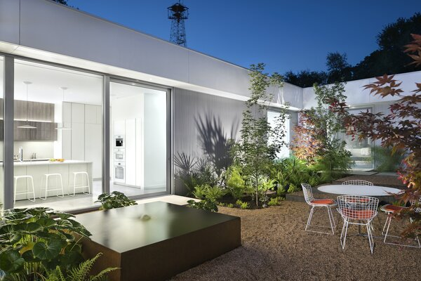 """The exterior palette of the rear addition is clean and modern. Smooth white stucco walls are punctuated by grey aluminum windows and corrugated aluminum panels. """"These two materials frame the landscape that will grow between and around them,"""" says architect Miguel Rivera."""