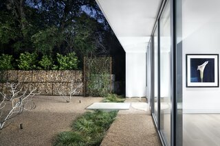 The fence surrounding the property consists of wire mesh that will become a visual screen as it is overtaken by ivy, and gabion walls that contrast with the sleek materiality of the architecture.