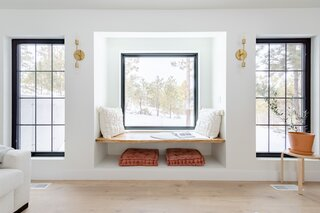 """The living area is oriented around a floating window seat crafted from oak. """"We wanted a place for guests to comfortably sit, read, and reflect in the beautiful Colorado surroundings,"""" says Tarah. """"We sourced the perfect slab of white oak from a local mill. We kept the edges raw and used a light, matte finish that highlighted the natural beauty without it being over saturated. I wanted it to feel as unfinished and natural as possible."""""""
