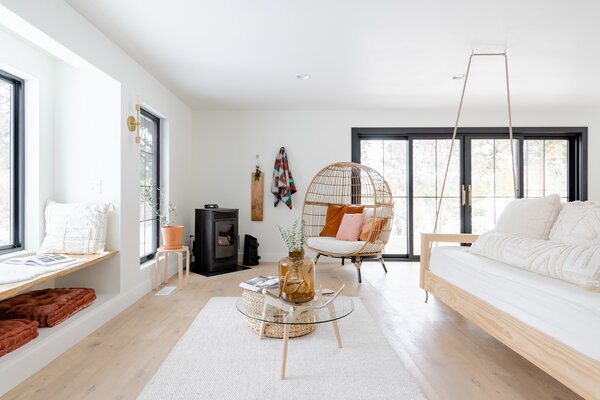 The main living area features a black pellet stove in the corner and a raw-edge, white oak window seat, which add rustic elements to the clean, bright space.