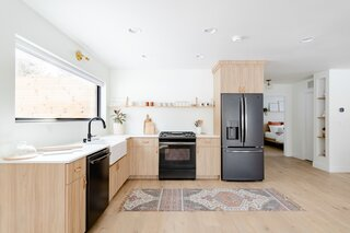 "The kitchen features organic materials, such as wood and leather, with a matte-white quartz counter. ""We wanted the space to feel uniquely warm and lived-in while achieving some modern aesthetic,"" says Tarah."