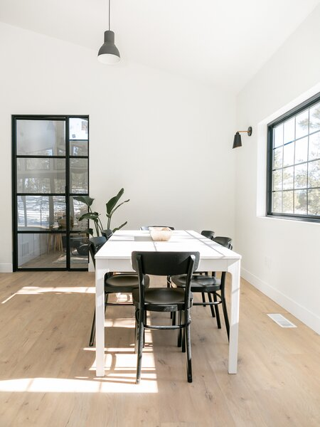 The main dining area in The House features a simple white dining table surrounded by black-painted chairs. The generous windows flood the space with natural light.