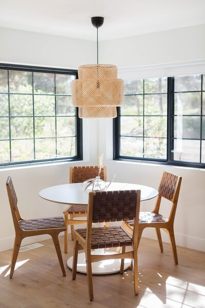 Leather dining chairs have been paired with a simple white, round table to create spatial and visual balance in the corner nook by the kitchen.