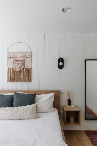 "The two guest rooms feature queen beds, cozy textiles, and thoughtful conveniences for guests such as reading lamps and hanging hooks. ""One way we married clean and rustic aesthetics was to install vertical shiplap behind the headboard in one of the rooms,"" says Tarah. ""We chose boards in irregular sizes with a rough-hewn finish to add texture and dimension to the feature wall."""