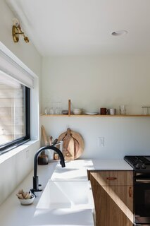 The shelves in the kitchen are crafted from pine and suspended using leather straps. These shelves display glasses, mugs, and a few select bowls, while everything else is neatly tucked away inside the cabinets, keeping the counters clear and drawing the eyes upward to the large horizontal window.