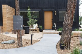 "When arriving at the property, a sign directs guests down one path for the workspaces (The Loft) and another for the guesthouse (The House). ""We knew that having separate entrances and not connecting the spaces internally would be the trick to keeping each space separate and private,"" says Tarah. ""We spent a lot of time thinking through the walking paths that led to each space and considering how to make them cohesive while serving different functions."""