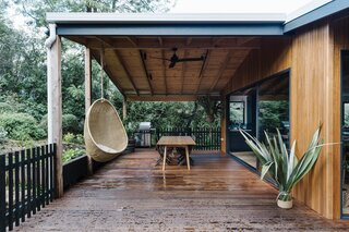 The new blackbutt timber deck has been designed for entertaining, al fresco dining, and enjoying views of the garden and surrounding bushland. It features a large dining table, a hanging egg chair, and a barbecue.