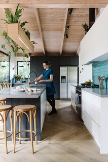 """""""My favorite aspect of the project would have to be the custom-built planter/light box suspended over the island bench,"""" says interior designer Kate Lucas. """"The cascading plants bring a gorgeous green accent to the interiors. I also have a soft spot for the herringbone floor."""" The custom planter box was built by local furniture maker and friend Lee Gratton of Gratton Design."""