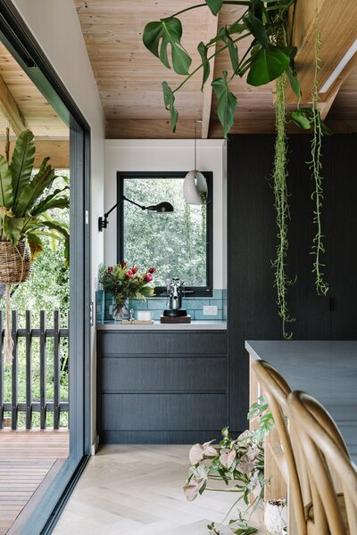 A coffee nook (featuring the same teal-blue tiles as the backsplash) is built into a corner of the kitchen next to the pantry, with a framed view of the eucalyptus trees that surround the home.