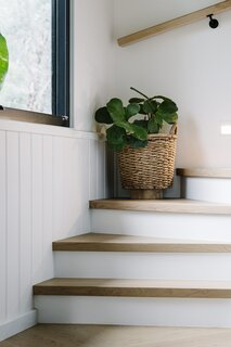 The new timber stairs wrap around the outer walls of the home, replacing the original staircase which divided the living and dining spaces on the ground floor. The new stairs allow the two spaces to be connected via an open plan.