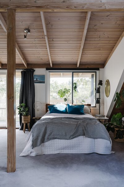 The master bedroom is located on the first floor and features a balcony overlooking a leafy canopy. The timber ceiling mirrors the one on the ground floor.