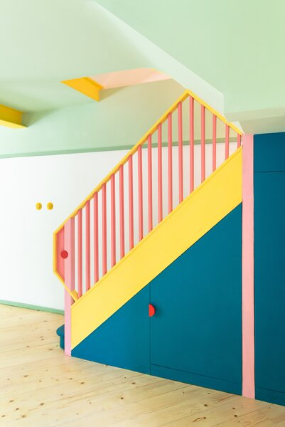 """The new pink-and-yellow banister features red circular """"eyes,"""" and the colors match the round yellow ROO light switches from Swtch."""