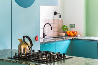 The kitchen backsplash features pink square Domus tiles framed by turquoise blue Mapei grout. The blue grout echoes the tones of the pale blue pantry and the teal cabinetry.