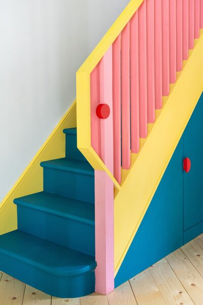 An angular yellow handrail folds over to meet a pink newel post, joined together by a red circular button. The stair is painted deep blue to accentuate its presence in the room.